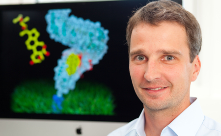 Michael Hothorn in front of a model image of a receptor kinase. Photo: Jörg Abendroth/MPI for Developmental Biology